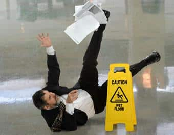 Man slipping on wet floor next to sign