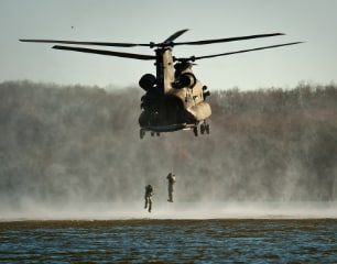 Helicopter lifting troops from a lake